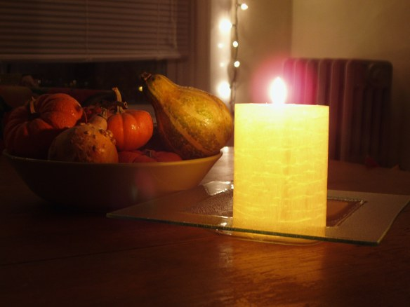 fall gourds and lit candle