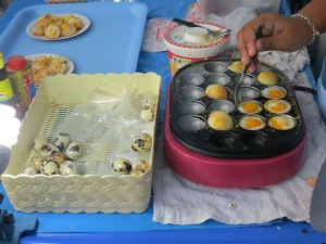 Cooking up quail eggs--which are then sprinkled with pepper and soy sauce, yum