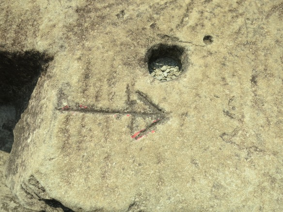 Not sure who carved the arrow--the ancients or modern restoration workers--but the hole was probably used to hold wooden pegs as stones were maneuvered into place, then removed when the stones were snugly fitted