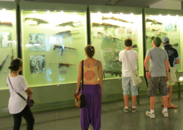 Visitors look at the guns on display